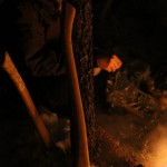 An axe proped up against a tree, as the prior users gather around the fire at their finished camp at Duck Lake in Yellowknife, NWT.