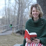 Erika Thompson looks up from her book to smile for the camera at Confederation Park in Calgary, Alberta.