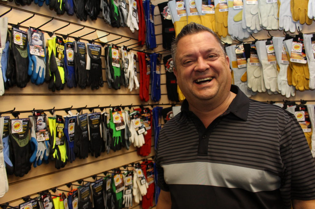 A photo of Watson Glove rep Randy Dreager standing in front of a display of his product. (Photo by Shane Weaver)